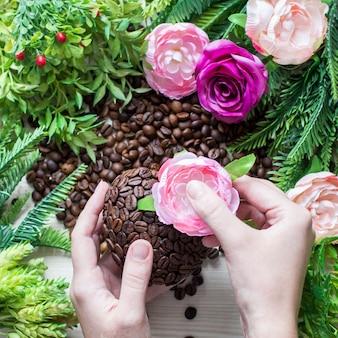 손, 꽃, 녹색 가지에 커피 콩의 심장