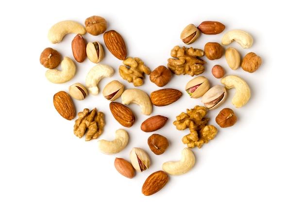 Сердце из разных орехов, выложенных на белой поверхности, вид сверху.