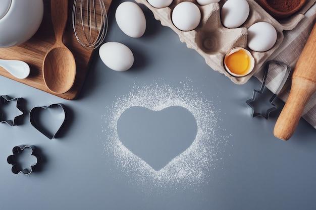 小麦粉と調理器具の心臓部。バレンタインデーのコンセプト。バレンタインデーのための自家製クッキーを作る、フラットレイ、トップビュー。灰色の背景で焼くための材料。