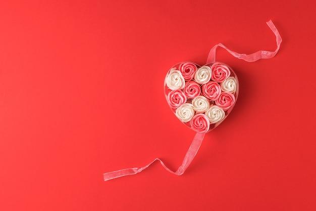 빨간색 배경에 리본 상자에 분홍색과 흰색 장미의 심장. 사랑의 개념.