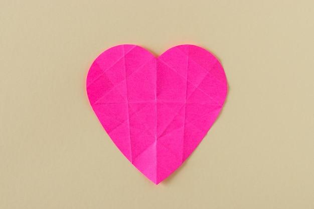 Сердце из розовой мятой бумаги на ярком фоне
