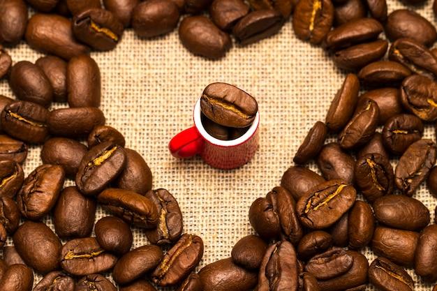 ローストコーヒー豆のハートと黄麻布の背景にカップ