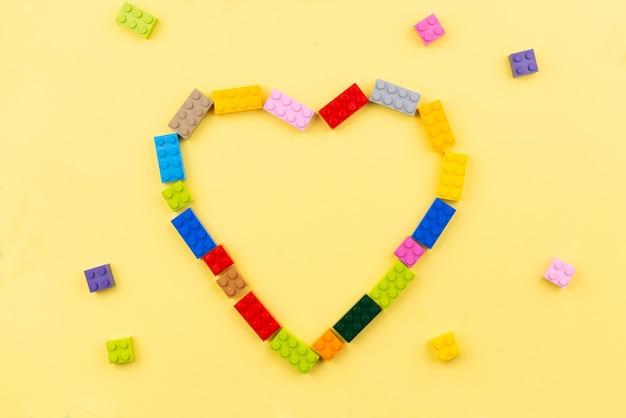 노란색 바탕에 장난감 색된 플라스틱 빌딩 블록의 심장