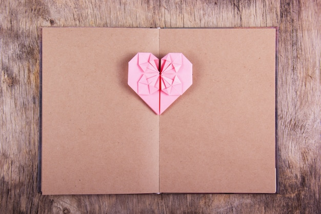 Heart origami and book with blank pages.