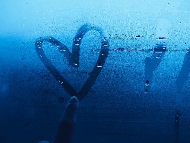 Сердце краска пальцем на стеклянном окне