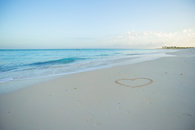 Heart painted in white sand on a tropical beach