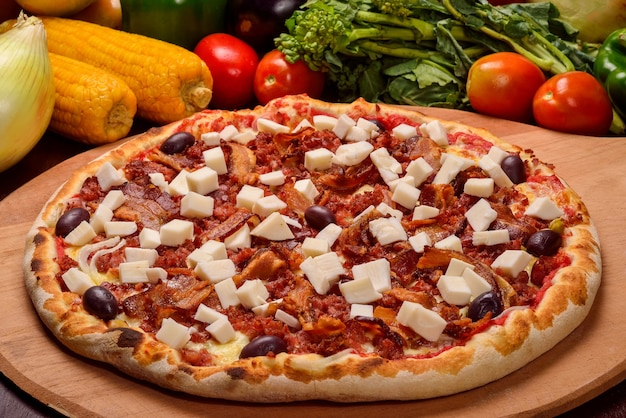 Heart of palm pizza with bacon on a wooden board and vegetables in the background.