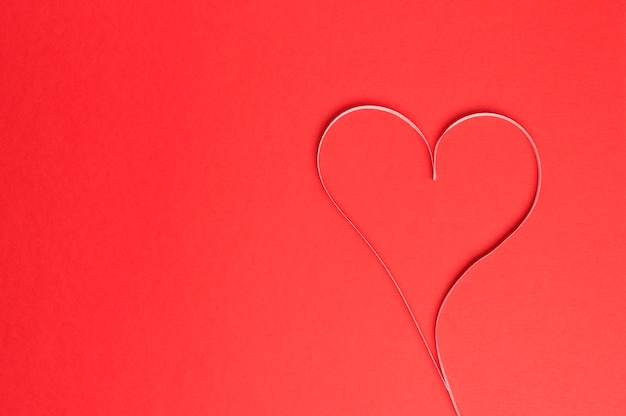 Heart of paper strips on a red background