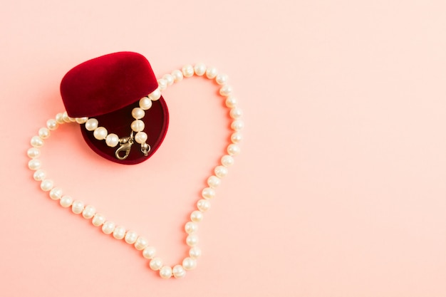 Heart of pearls necklace with opened gift box on pink background