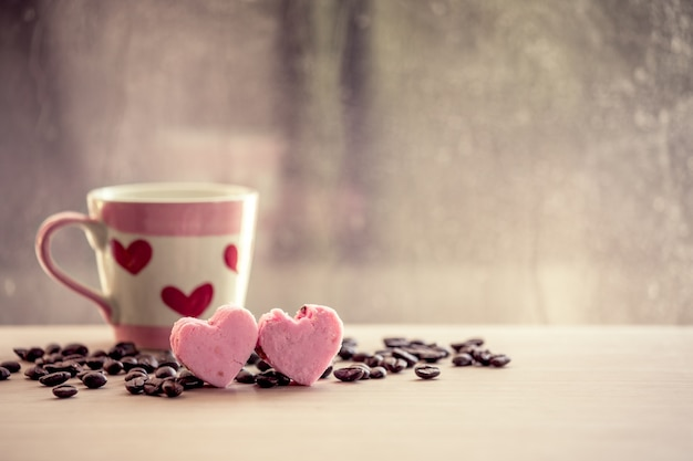 Heart pink cookies and coffee cup on rainy day window background in vintage color tone