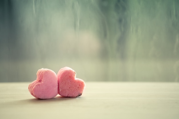 Heart pink cookies on rainy day window background in vintage color tone