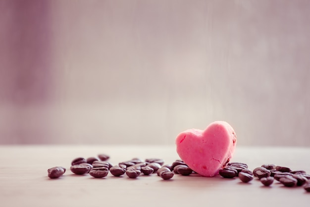 Heart pink cookies with coffee bean on rainy day window background in vintage color tone