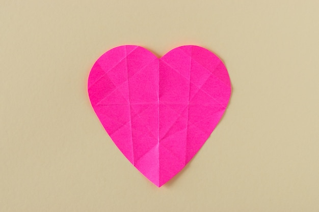 Heart of pink crumpled paper on a bright background