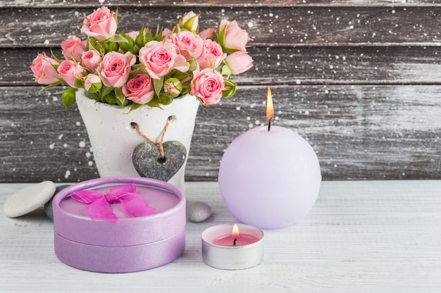 Heart, pink roses in concrete pot with candles