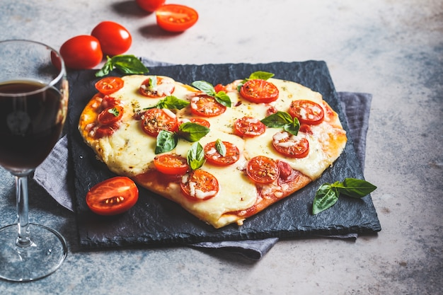 Heart pizza with mozzarella and tomatoes on a slate