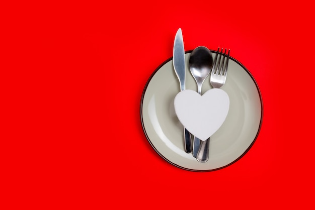 Heart on plate and silver wear on red.
