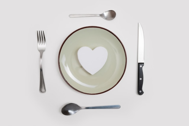 Heart on plate and silver wear on white.