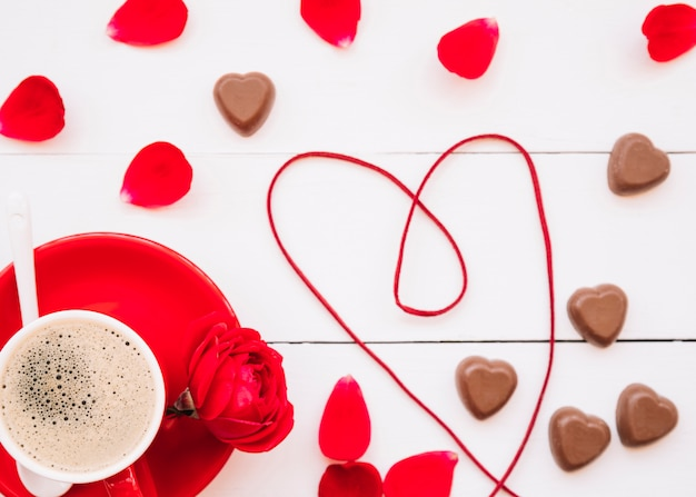 Heart of ribbon near chocolate sweet candies, cup on plate and petals