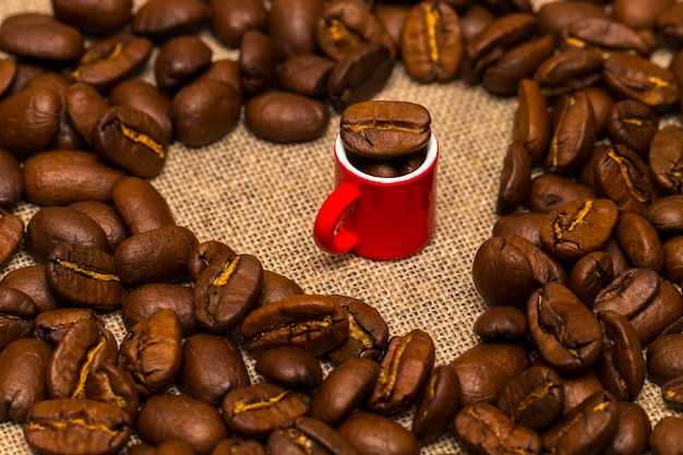 Heart of roasted coffee beans and a cup on burlap background