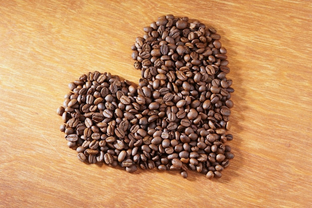 Heart roasted coffee beans on wooden background
