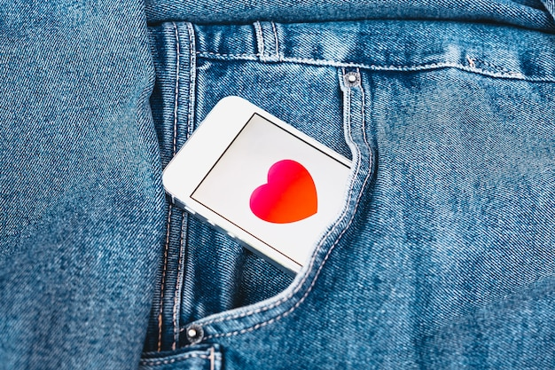 Heart on the screen of a mobile phone sitting in a jeans pocket