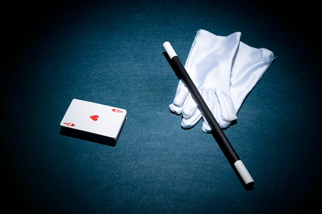 Heart shape aces card; magic wand and white pair of gloves over poker table