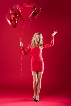 Heart shape balloons held by a woman
