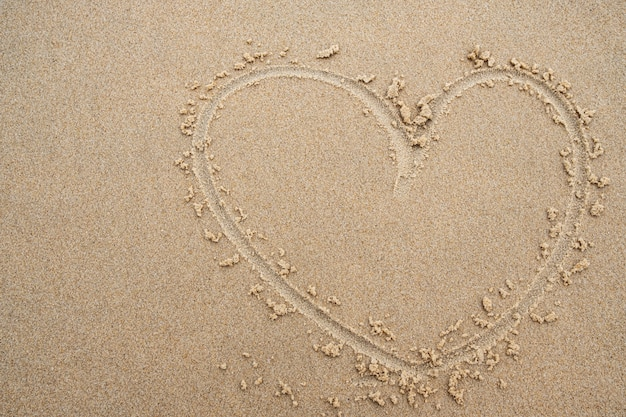 Heart shape on the beach sand background.