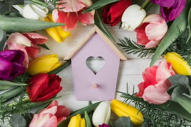 Heart shape bird house surrounded with colorful tulips on wooden desk