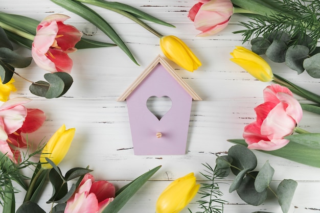 Heart shape bird house surrounded with pink and yellow tulips on white wooden desk