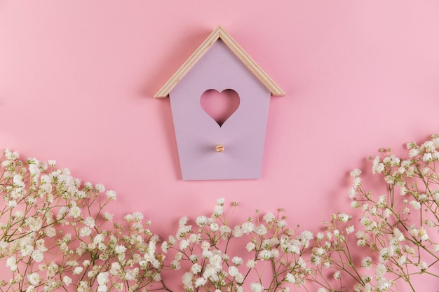 Heart shape bird house with decorated gypsophila flowers on pink background
