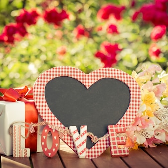 Пробел классн классного в форме сердца, подарочная коробка и цветы на фоне весны. концепция дня матери