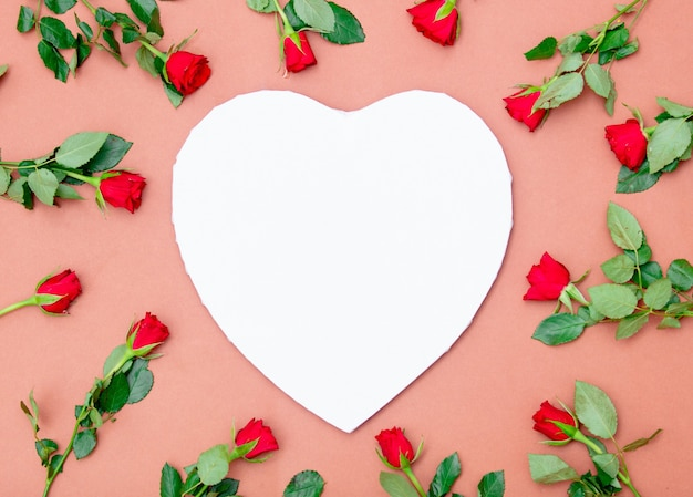 Heart shape cardboard and red roses on pink