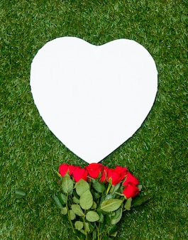 Heart shape cardboard and roses bouquet on green grass.