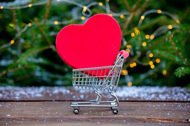 Heart shape in cart on wooden table with spruce tree
