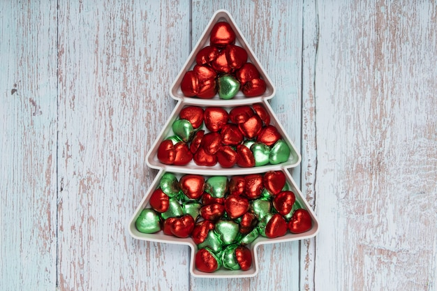 Heart shape chocolate candies on a pine shape plate with red and green christmas colors