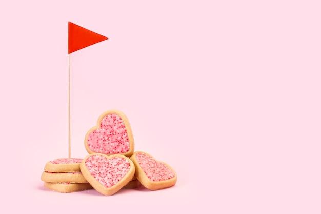 Печенье в форме сердца с красным флагом на розовом фоне