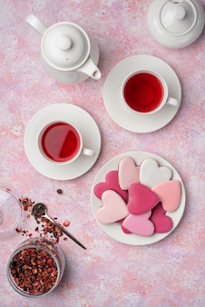 Heart shape cookies with icing with berry tea. concept: valentine's day tea party, festive table setting in pink.