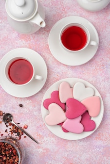 Heart shape cookies with icing with berry tea