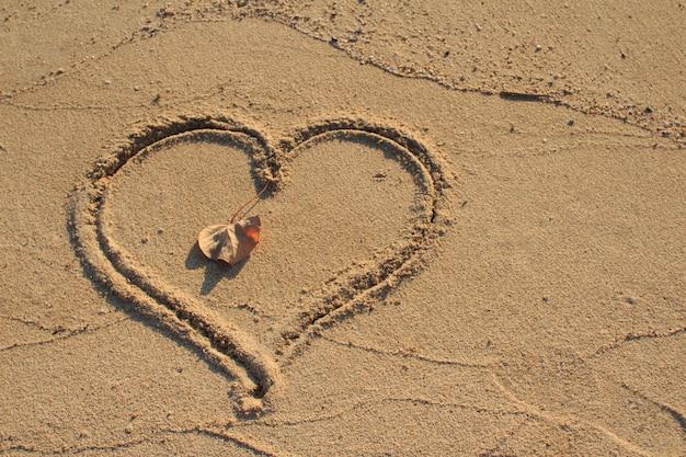 Heart shape drawn on beach sand