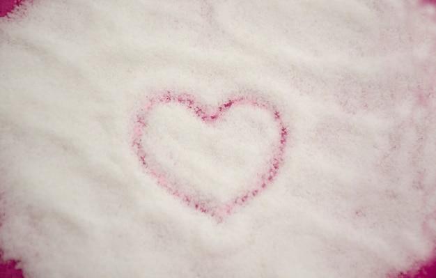 白いグラニュー糖の背景に描かれたハートの形