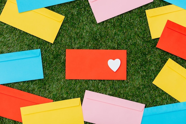 Heart shape and envelopes on green grass.