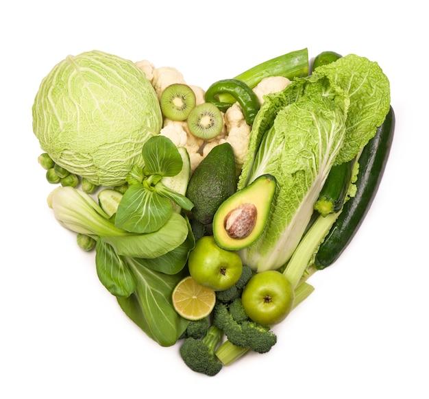 コピースペースのある様々な野菜によるハート型のフォルム。白い背景の上のサラダレシピのためのきゅうり、ピーマン、ズッキーニ