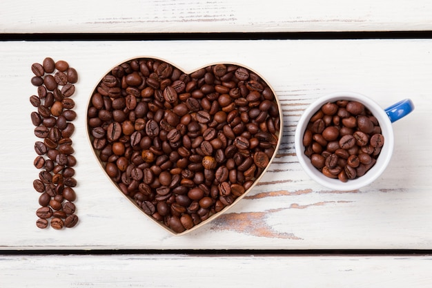 Heart shape form and cup filled with roasted coffee grains. i love natural fresh coffee. white wooden planks on surface.