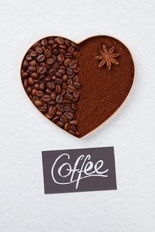 Форма в форме сердца из кофейных зерен и порошка растворимого кофе. изолированные на белой поверхности