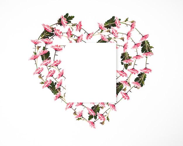 ピンクの花で作られたハート型のフレームにメモ用紙、バレンタインデーのグリーティングカード