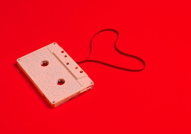Форма сердца от аудиокассеты над красной бумагой.