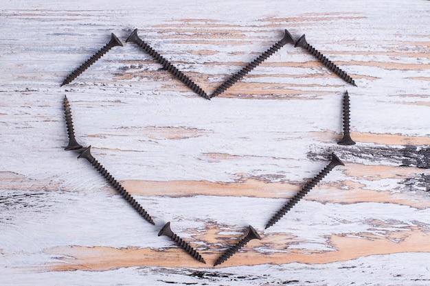 Форма сердца из черных винтов на деревянном фоне