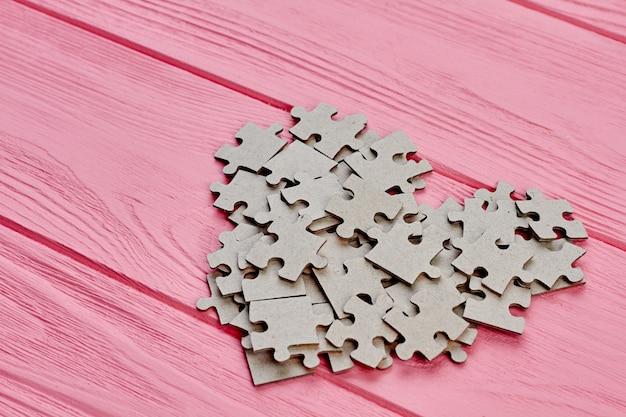 Форма сердца из картонного лобзика. серые головоломки головоломки, образуя форму сердца на розовом деревянном фоне. концепция любви и романтики.