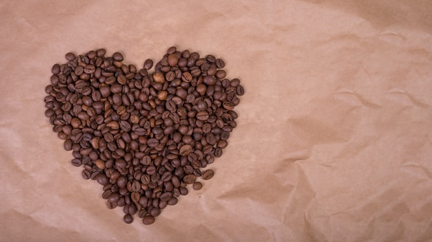 Heart shape from coffee beans on paper